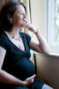 Pregnant woman staring out window